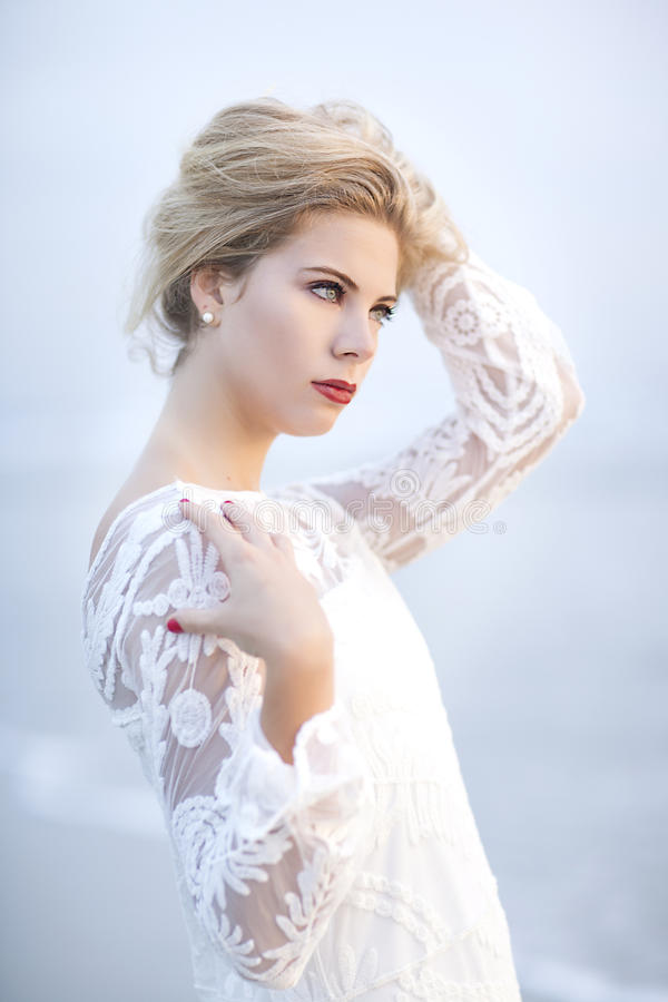 A beautiful blond woman with her hair up and lace dress on the beach in St.Augustine, Florida. stock images