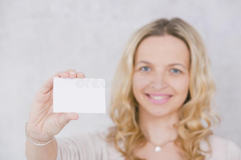 beautiful blond woman is holding white card for copy space in front of grey background royalty free stock photos