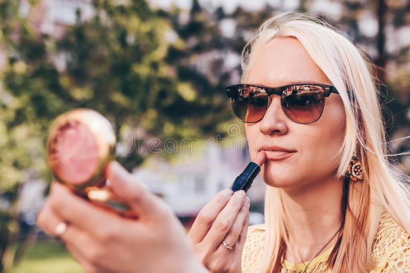 Beautiful blond woman loking in the small mirror and painted her lips. Make up concept in the street stock photo