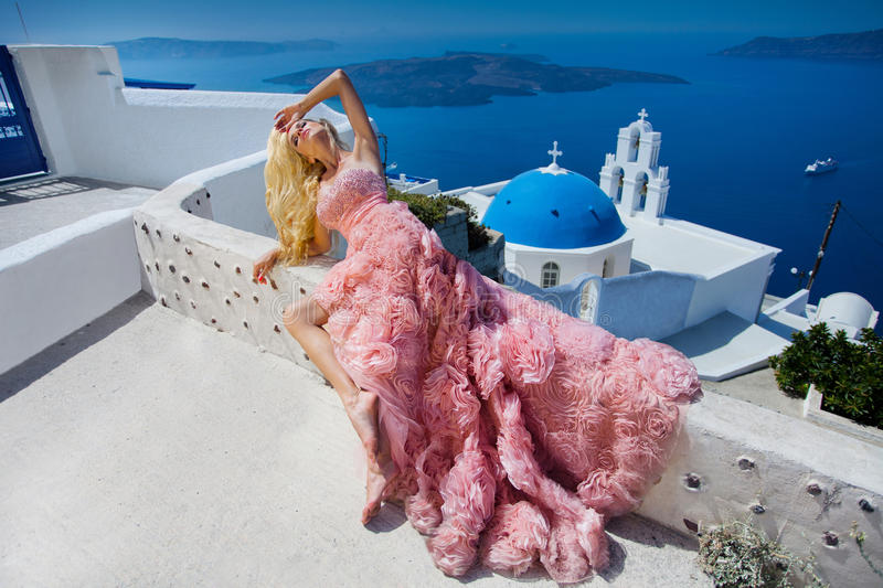 Beautiful blond woman with long legs in a pink ball gown. Beautiful blond woman in pink ballroom dress lies on a background of a beautiful view of the stock photos