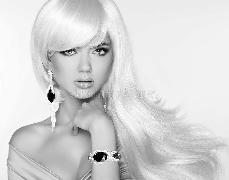 Beautiful blond woman model with long wavy hair. Luxury Jewelry. royalty free stock photography