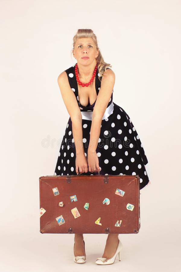 Beautiful blond woman in pinup style, dressed in a polka-dot dress, stands and hardly holds a heavy suitcase, white background stock image