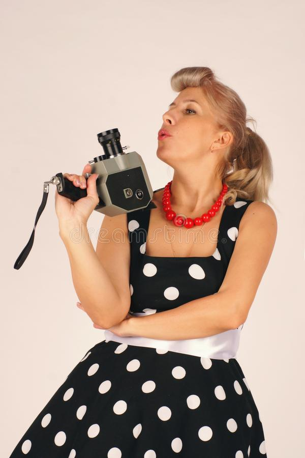 Beautiful blond woman in pinup style, dressed in a polka-dot dress, stands and holds a retro camera with one hand with a royalty free stock image