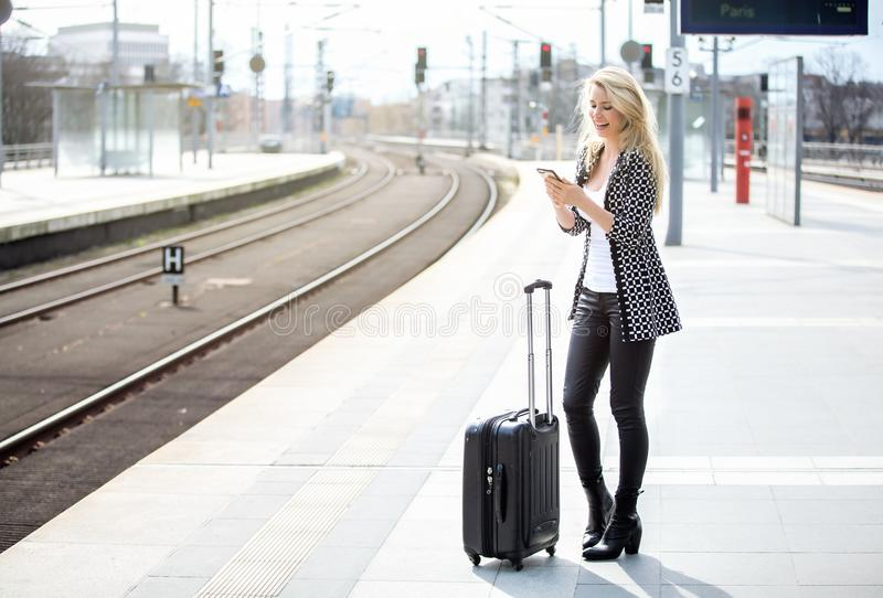 Beautiful blond woman is reading a sms at the train station.  stock photos