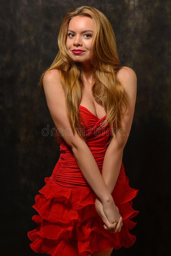 Beautiful blond woman in red dress standing bent arm lock. royalty free stock photo
