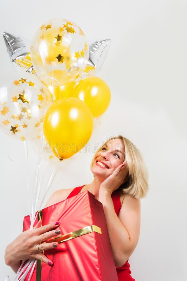 Beautiful blonde woman holding a gift and balloons on a white background stock images