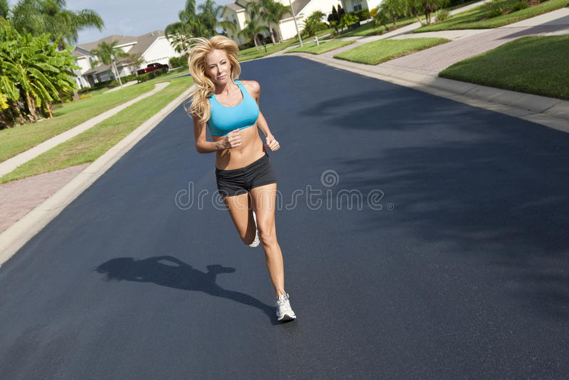 Beautiful Blond Woman Running In Suburban Street stock photos