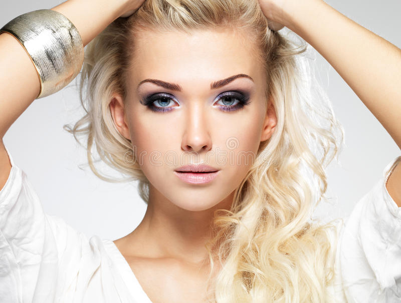 Beautiful blond woman with saturated makeup. Fashion model posing in studio. Portrait of a beautiful blond woman with saturated makeup. Girl posing on white royalty free stock images
