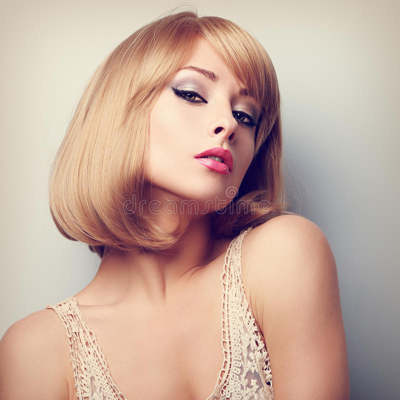 Beautiful blond woman with short hairstyle posing. Color portrait royalty free stock photos