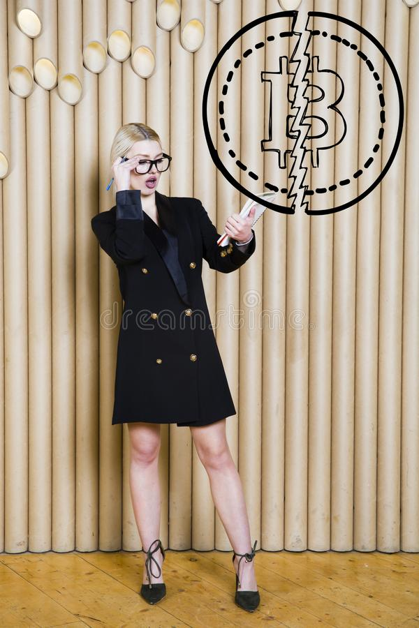Beautiful blond woman showing standing near bitcoin sketch. Virtual money or btc crush concept. Cryptocurrency. royalty free stock photography