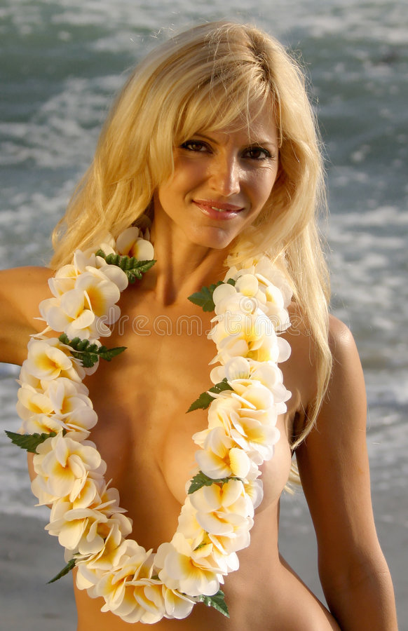 Beautiful Blond Woman smiling while wearing a Lei. On the Beach at Sunset royalty free stock image