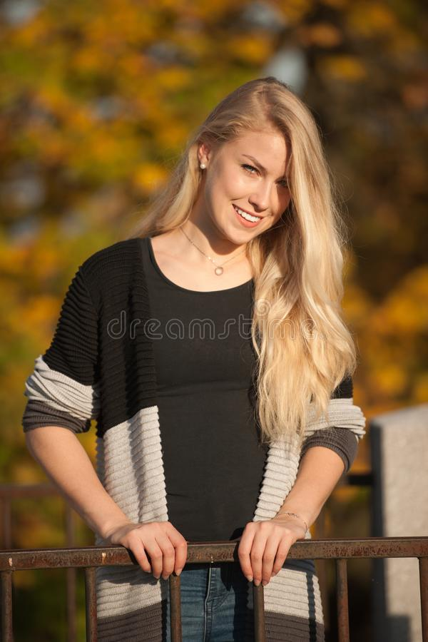 Beautiful blond woman sitting on sitting on a log in the forest in autumn royalty free stock photos