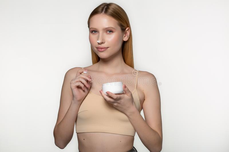 Beautiful blond woman tender jar of moisturizer cream. Close-up fresh young woman face. Isolated on white royalty free stock images