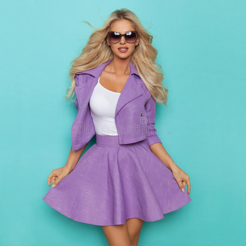 Beautiful Blond Woman In Violet Mini Skirt, Jacket And Sunglasses. Is posing and looking at camera. Three quarter length studio shot on turquoise background royalty free stock photography