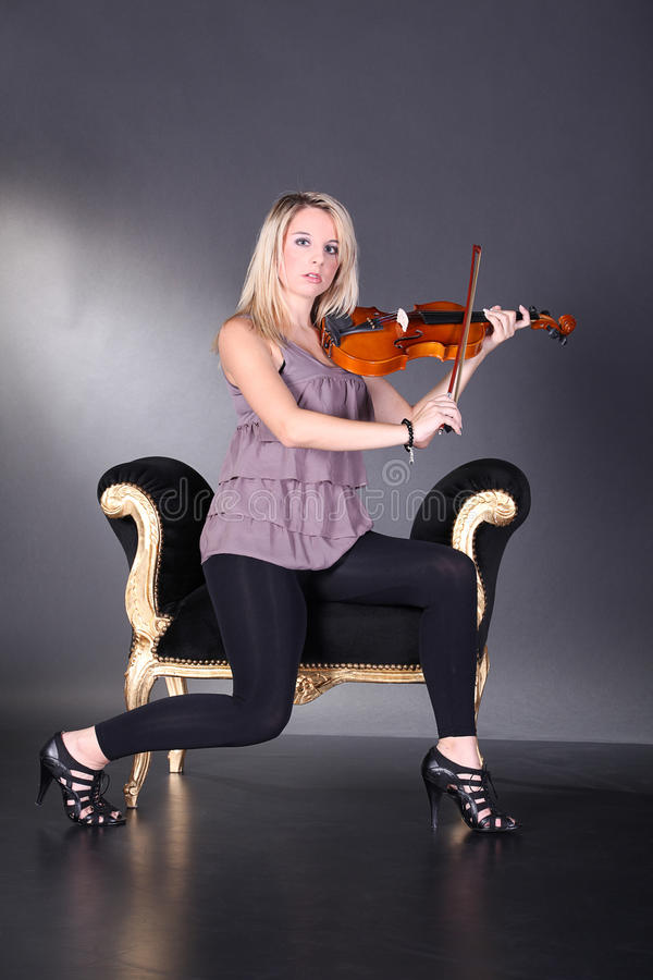 Beautiful blond woman with violin. On baroque armchairs royalty free stock images