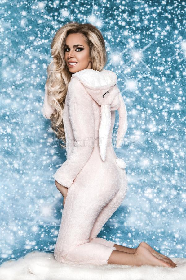 Beautiful blond woman wearing a winter pajama, a bunny costume, smiling happily. Fashion model in Easter bunny costume. Christmas royalty free stock photography