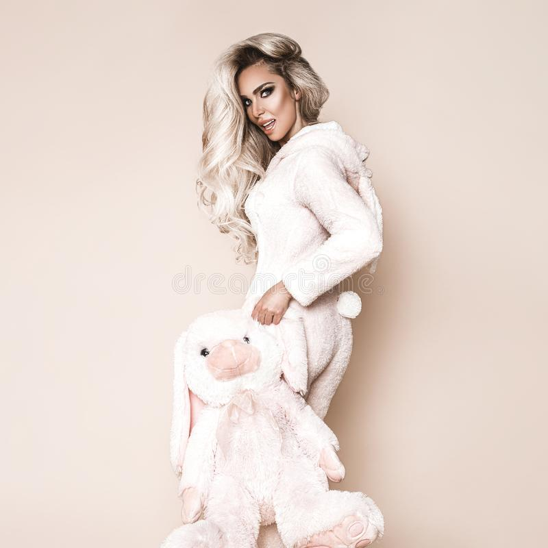 Beautiful blond woman wearing a winter pajama, a bunny costume, smiling happily. Fashion model in Easter bunny costume. Christmas stock photos