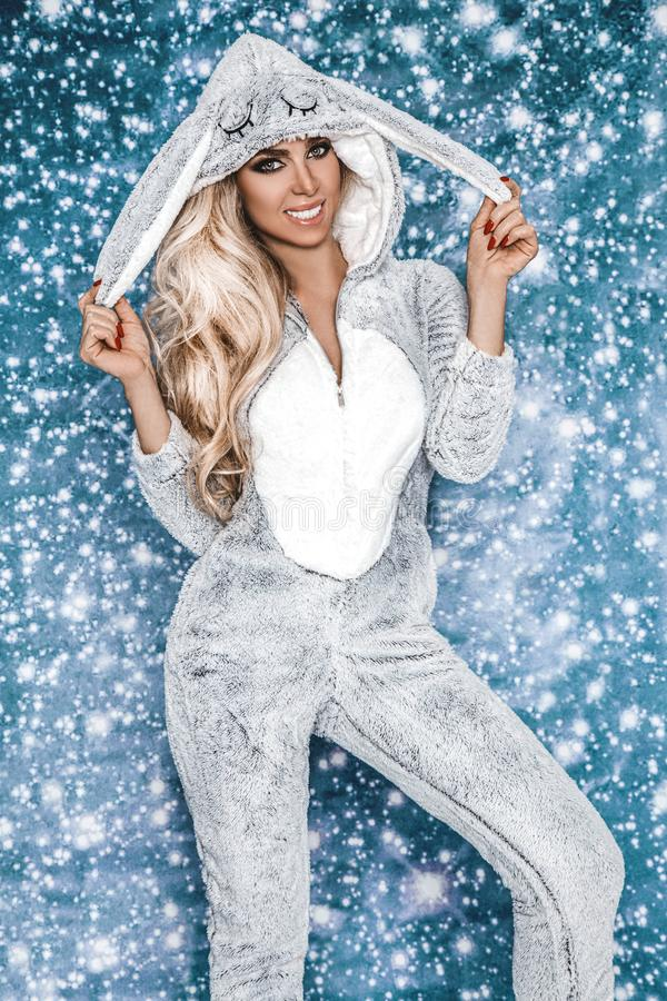 Beautiful blond woman wearing a winter pajama, a bunny costume, smiling happily. Fashion model in Easter bunny costume. Christmas stock image