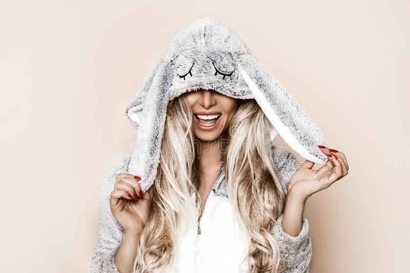 Beautiful blond woman wearing a winter pajama, a bunny costume, smiling happily. Fashion model in Easter bunny costume. Christmas royalty free stock photo