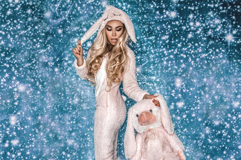 Beautiful blond woman wearing a winter pajama, a bunny costume, smiling happily. Fashion model in Easter bunny costume. Christmas stock images
