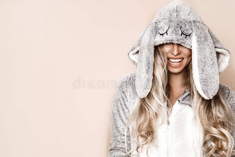 Beautiful blond woman wearing a winter pajama, a bunny costume, smiling happily. Fashion model in Easter bunny costume. Christmas. And Easter concept stock photography