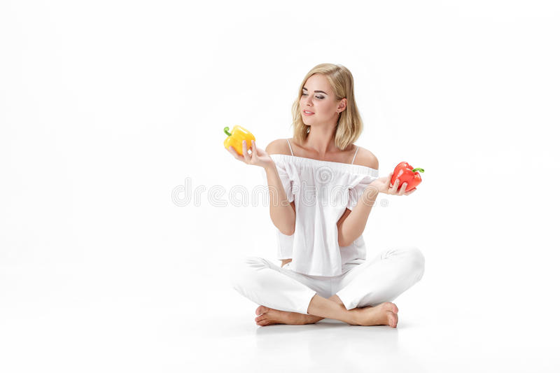 Beautiful blond woman in white blouse chooses yellow or red bell pepper. Health and Diet stock image