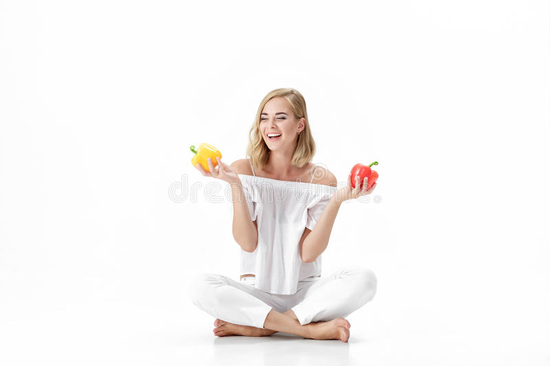 Beautiful blond woman in white blouse holding yellow and red bell pepper. Healthy diet and diet royalty free stock images