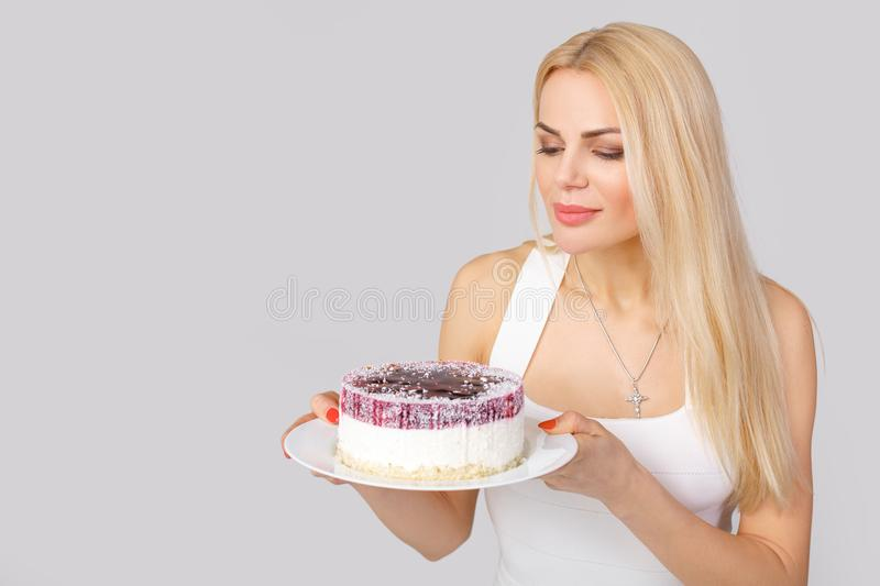 Woman in white dress holding cake stock images
