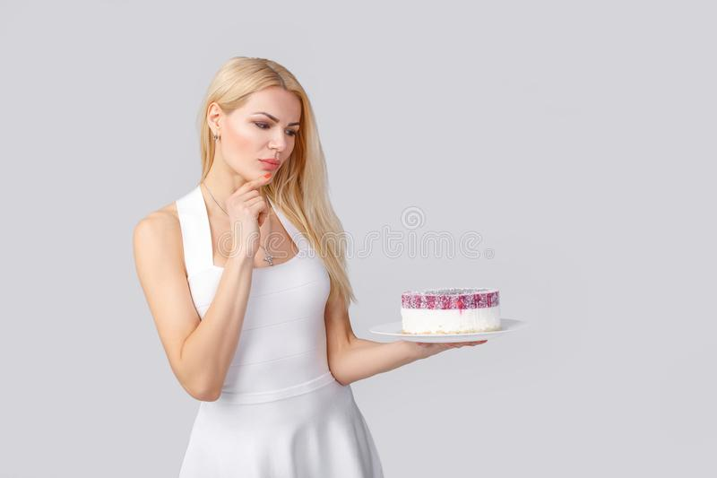 Woman in white dress holding cake royalty free stock photo