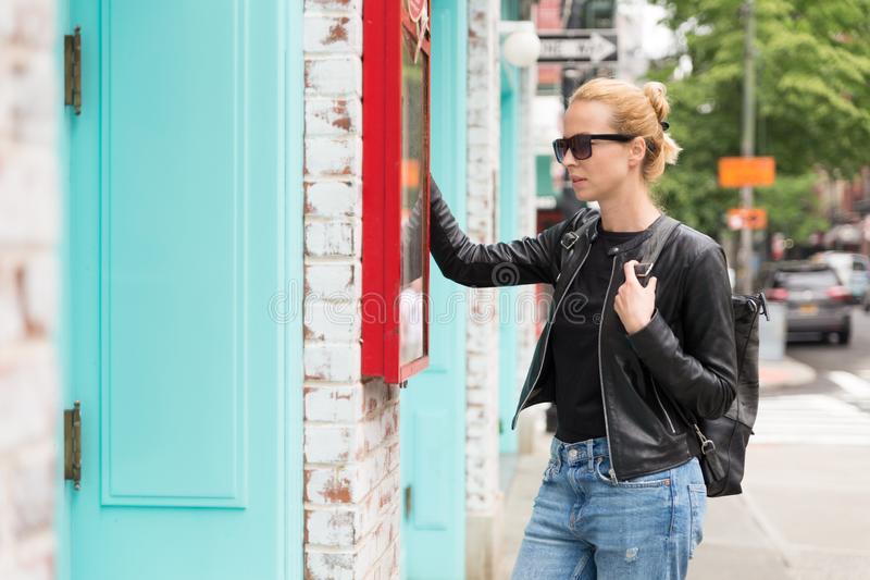 Beautiful blond young female tourist checking restaurant menu outdoors on city break weekend trip in New York City. United States of America stock photo