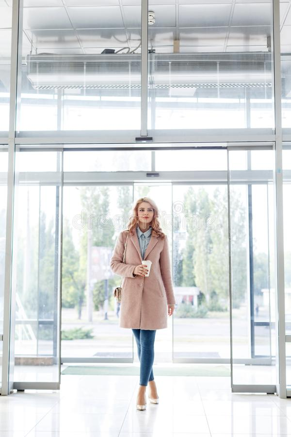 Beautiful blond young girl in a beautiful beige coat, jeans and high heels. royalty free stock photos