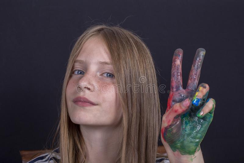 Beautiful blond young girl with freckles and hands painted in colorful paints indoors on black background, closeup portrait royalty free stock photos