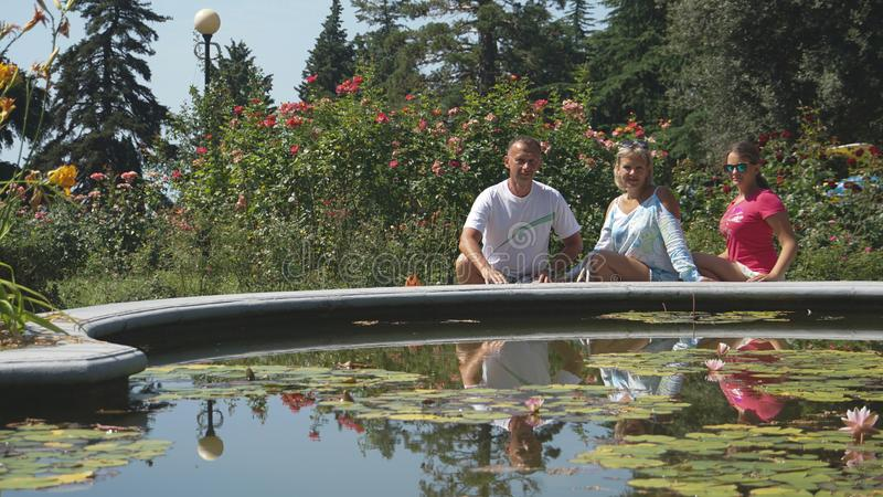Mother, father and cute daughter in summer near fountain with water lilies. Beautiful blond young mother, father and cute daughter in summer near fountain with royalty free stock photo