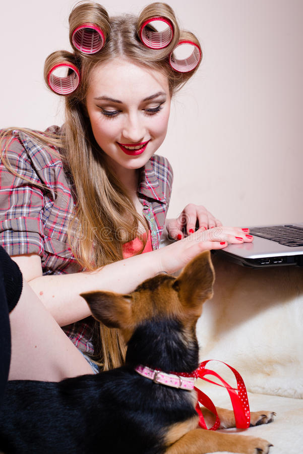 Beautiful blond young pinup woman having fun playing with cute small dog relaxing lying in bed typing on laptop stock image
