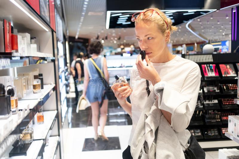 Beautiful blond young woman choosing perfume in retail store. Lady testing and buying cosmetics in beauty store stock photos