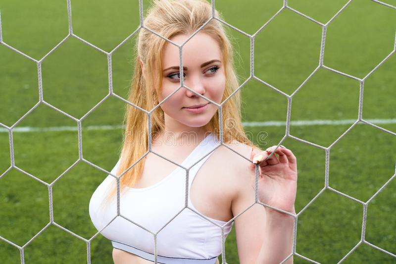 Beautiful blond woman in goalkeeper net royalty free stock photography