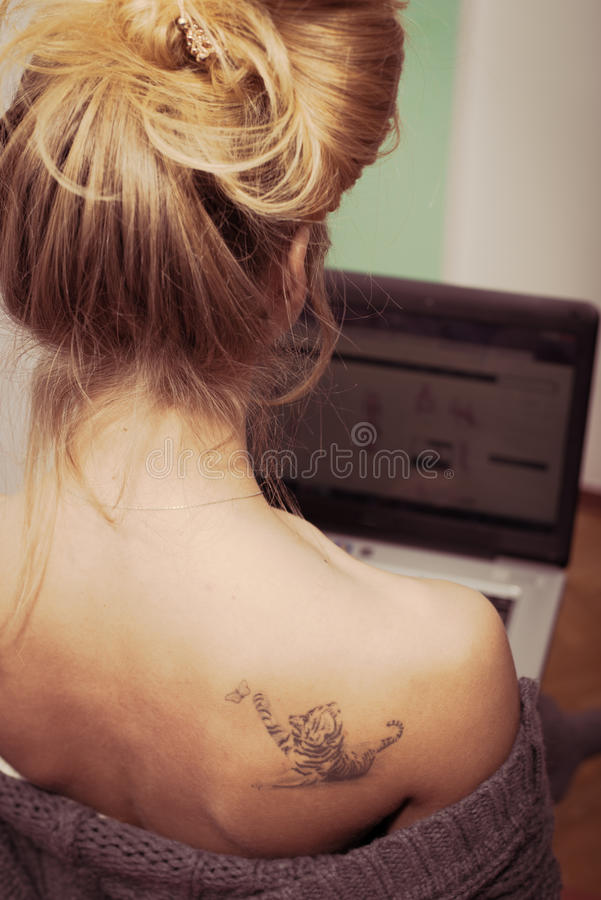 Beautiful blond young woman works on laptop pc stock image