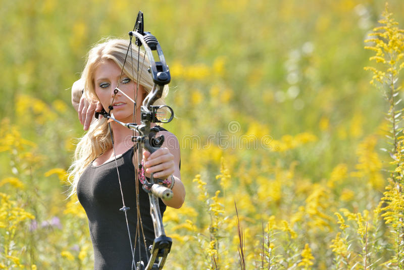 Beautiful blonde archer in field of wildflowers royalty free stock image