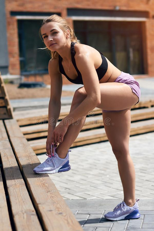 Beautiful blonde athlete girl ties her shoelaces, looking at the camera royalty free stock image