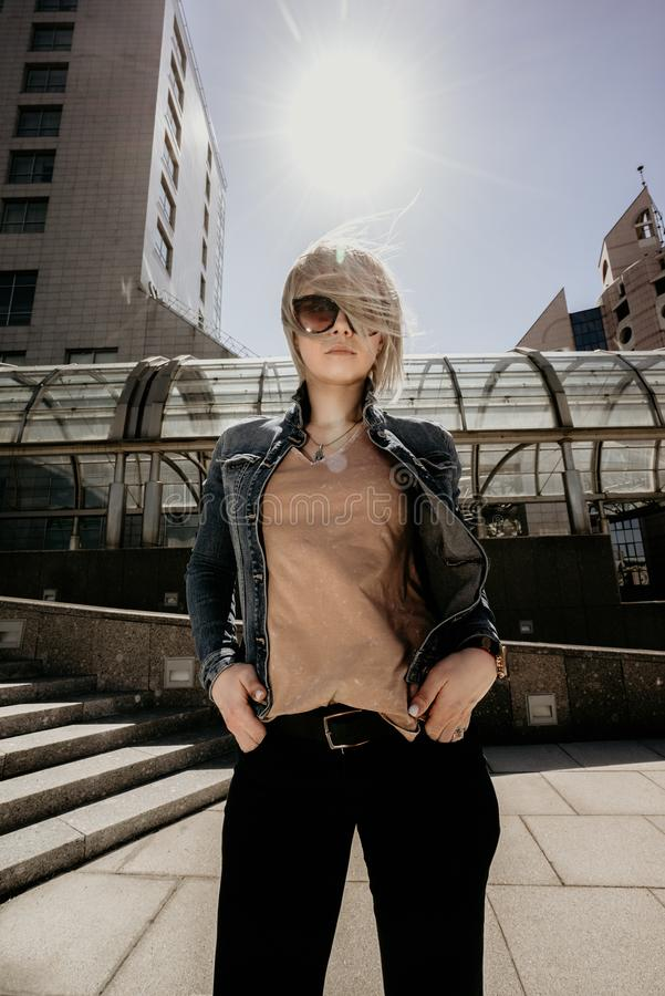 Beautiful blonde on the background of a modern city in sunny windy weather looking into the camera. Portrait of a modern stock photo