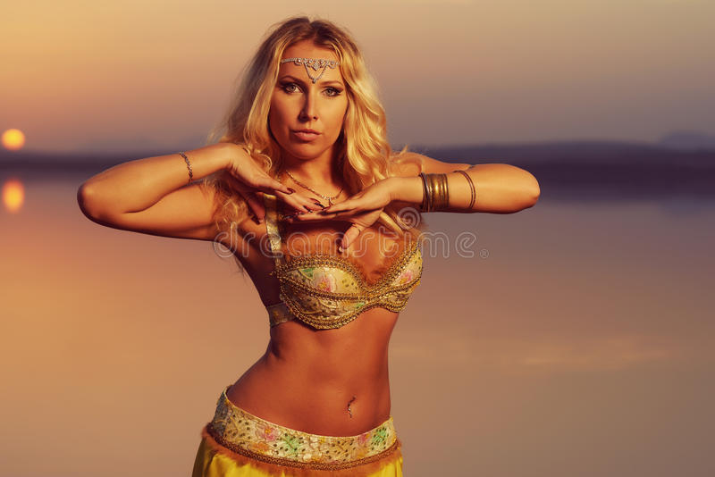 Beautiful blonde belly dancer woman. On a lake in the evening. Golden colors stock photography