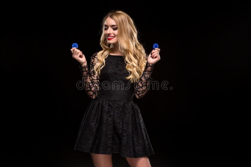 Beautiful blonde in a black dress with casino chips in hands isolated on a black background. Poker. Casino. Roulette Blackjack Spin. Caucasian young woman is stock image