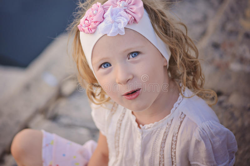 Beautiful blonde blue eyed child girl portrait in pink and white headband royalty free stock image