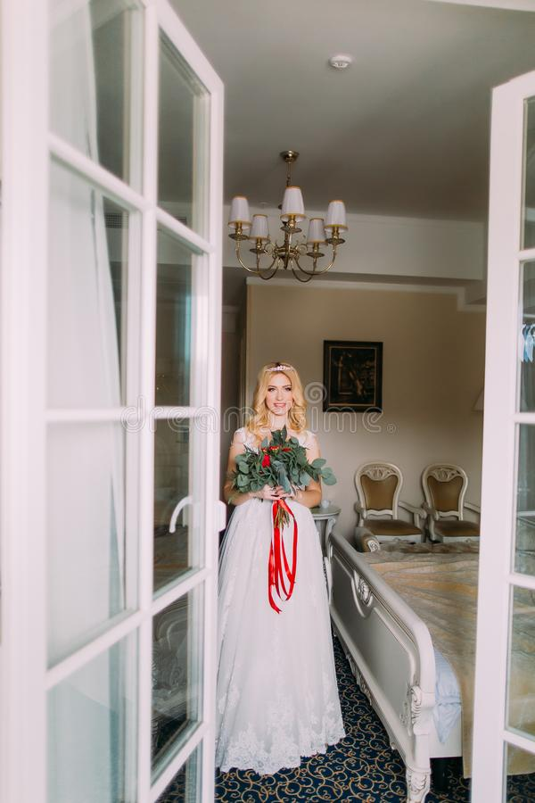 Beautiful blonde bride with bouquet of red roses standing near the window stock photo