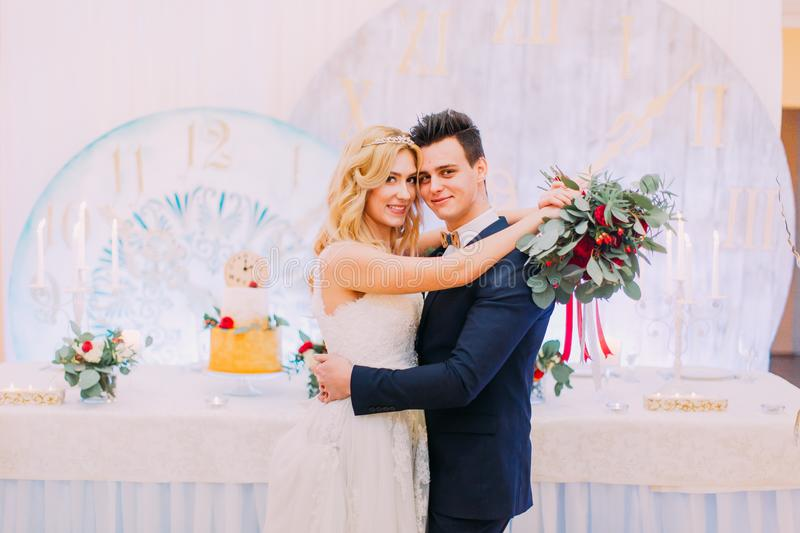 Beautiful blonde bride and groom softly hug with bouquet of roses in the restaurant. royalty free stock images
