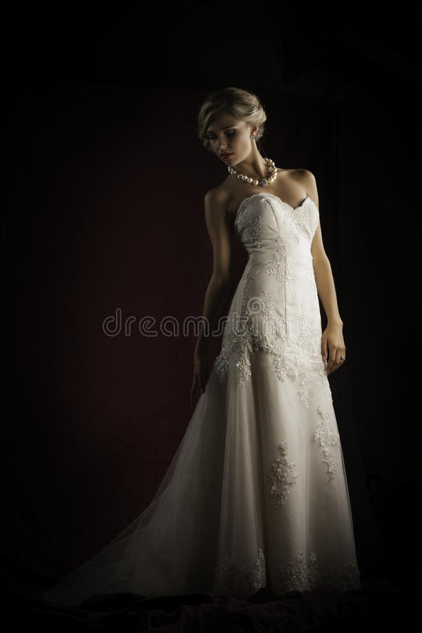 Beautiful blonde bride wearing vintage strapless wedding gown stock photos