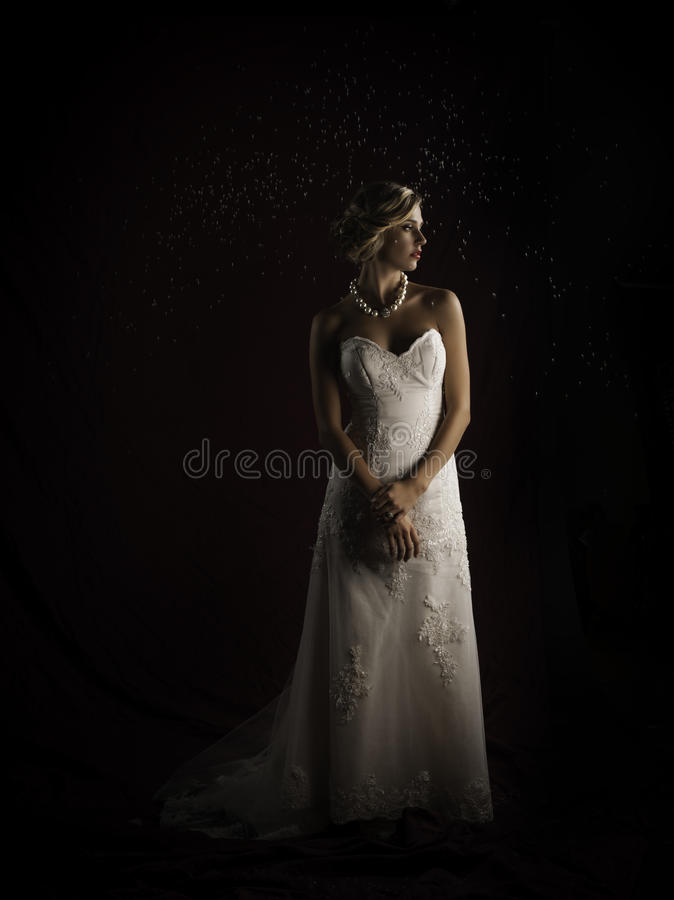 Beautiful blonde bride wearing vintage strapless wedding gown standing in the rain. Portrait of a beautiful young Caucasian bride wearing a strapless ivory color stock photos