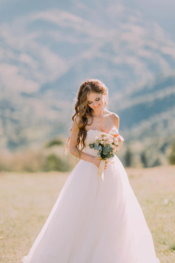 Beautiful blonde bride with wedding bouquet of flowers outdoors on mountain background stock image