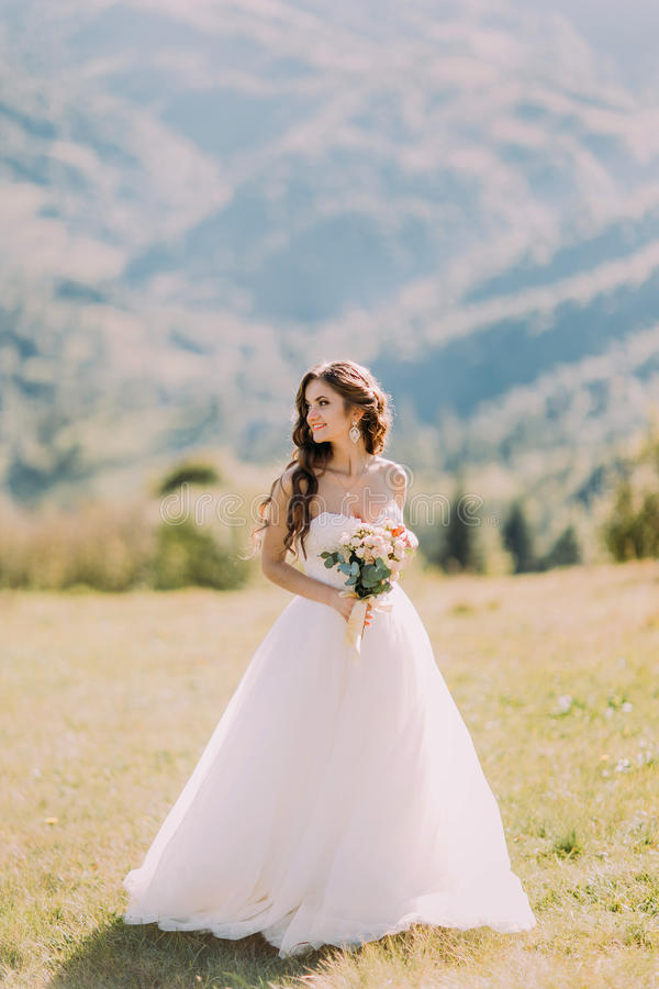 Beautiful blonde bride with wedding bouquet of flowers outdoors on mountain background.  royalty free stock image
