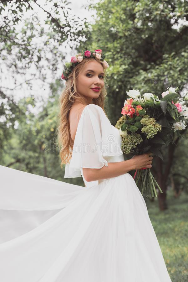 beautiful blonde bride in wedding dress and floral wreath holding bouquet of flowers and smiling royalty free stock photography